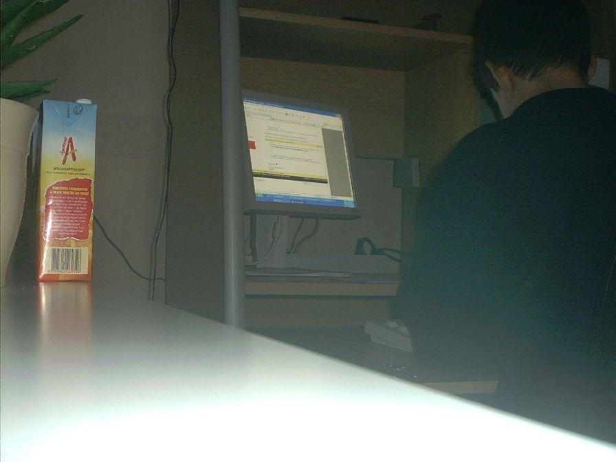 Achter de computer met pak appelsientje sinaasappelsap.